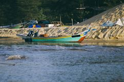 Traditional fisherman boat moored over beautiful sea view and sandy beach under bright sunny day Stock Photography