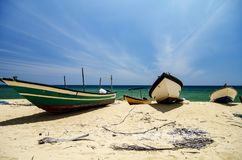 Traditional fisherman boat stranded on deserted sandy beach under bright sunny day. Beautiful scenery, traditional fisherman boat stranded on deserted sandy Stock Image