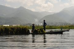 Traditional fisherman of Inle Lake. Fisherman in traditional costume fishing in balance, with a net, in a typical Inle lake canoe. Myanmar royalty free stock photography