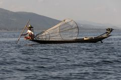 Traditional fisherman of Inle Lake. Fisherman in traditional costume fishing in balance, with a net, in a typical Inle lake canoe. Myanmar stock photos