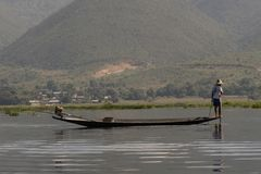 Traditional fisherman of Inle Lake. Fisherman in traditional costume fishing in balance, with a net, in a typical Inle lake canoe. Myanmar royalty free stock image