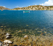 Traditional fishing boat on azure crystal clear sea water in bay of Simi island, Greece Royalty Free Stock Images