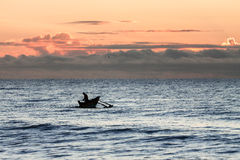 Traditional fishing boat with fisherman at sunrise Royalty Free Stock Photo