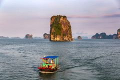 Traditional fishing boat in Halong Bay in a purple sunset, UNESCO world natural Heritage, Vietnam. Vietnamese traditional fishing boat in Halong Bay in a purple stock photography