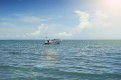 Traditional fishing boat laying alone on the sea,selective focus,filtered image,light and flare effect added.  royalty free stock images