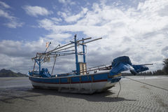 Traditional fishing boat laying on a beach near the sea with cloud and blue sky in background, dramatic colourful picture style Stock Photo