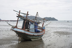 Traditional fishing boat laying on a beach near the sea with mountain and island, selective focus,filtered image Royalty Free Stock Image