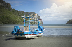 Traditional fishing boat laying on a beach near the sea with mountain and island Stock Photo