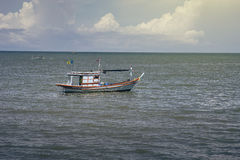 Traditional fishing boat laying on the sea,selective focus,filtered image,light effect added.  stock photography