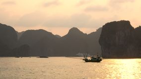 Traditional fishing boat sailing at sunset, Ha Long Bay, Cat Ba National Park, Vietnam. Traditional fishing boat sailing at sunset, with a cruise ship in the stock video footage