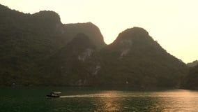 Traditional fishing boat sailing at sunset, Ha Long Bay, Cat Ba National Park, Vietnam. Traditional fishing boat sailing at sunset, through the limestone islands stock footage