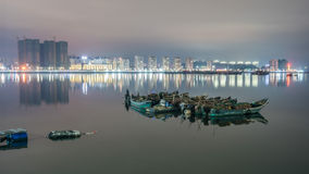 Traditional fishing boats and city lights Stock Photos