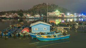 Traditional fishing boats and city lights Royalty Free Stock Photo