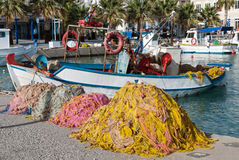 Traditional fishing boats in Greece. Traditional wooden boats and fishing nets in the harbor on October 12, 2013 in Kos island, Greece. Fishing in wooden Stock Photos