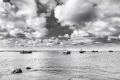 Traditional fishing boats in harbour with the ocean and clouds i. N the background Stock Photo