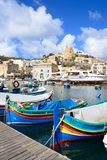Boats in Mgarr harbour, Gozo. Traditional fishing boats in the harbour with the Our Lady of Lourdes church on the hillside to the rear, Mgarr, Gozo, Malta Stock Photography
