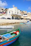 Fishing boats in Mgarr harbour, Gozo. Traditional fishing boats in the harbour with the Our Lady of Lourdes church on the hillside to the rear, Mgarr, Gozo Stock Image