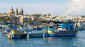 Traditional fishing boats luzzu and churches in Marsaxlokk. Malta Royalty Free Stock Photo