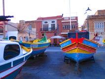 Boats ashore in Marsaxlokk in Malta. Traditional fishing boats pulled to shore in Marsaxlokk in Malta Stock Image