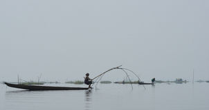 Woman on canoe Fishing in lake. Authentic village lifestyle-Fisher woman balancing wooden canoe with traditional Fishing Gear at Loktak Lake Manipur, Largest Stock Image