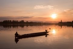 Traditional fishing pirogue at sunset on the Huai Luang Reservoir royalty free stock photography
