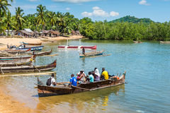 Traditional fishing village on Nosy Be island with wooden dugout. Ambatozavavy, Nosy Be, Madagascar - December 19, 2015: Traditional wood pirogue with outrigger Royalty Free Stock Photos