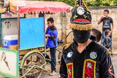 Traditional folk dancer & ice cream seller, Guatemala. Parramos, Guatemala - December 28, 2016: Traditional folk dancer in costume & ice cream seller in village royalty free stock photography