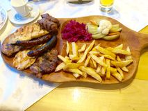 Traditional food. Imagine showing a rustic plate with traditional Romanian food consisting in 4 types of meat, fried potatoes and traditional pickles stock photos
