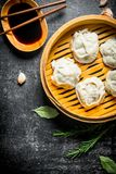 Traditional food. Manta dumplings in bamboo steamer with soy sauce. On dark rustic background stock photography