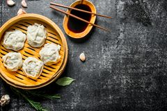 Traditional food. Manta dumplings in bamboo steamer with soy sauce. On dark rustic background stock photos