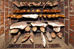 Traditional food. Smoked meat hanging in domestic smokehouse Royalty Free Stock Photo