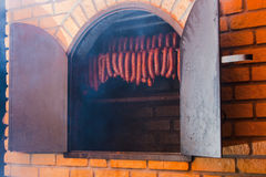 Traditional food. Smoked sausuages in smokehouse. Traditional food. Smoked sausages meat hanging in domestic smokehouse stock photography