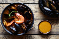 Traditional France Bouillabaisse fish soup with prawns, mussels tomato, lobster. Sauce Rouille. Rustic style background. Royalty Free Stock Photo