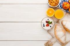 Traditional french breakfast background copy space. Traditional french breakfast menu background. Yogurt with fresh berries, glass of orange juice, muesli and Royalty Free Stock Photo