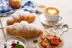 Traditional french breakfast menu closeup. Yogurt with fresh berries, cup of coffee, muesli and croissants on wooden table Royalty Free Stock Images