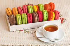 Traditional french colorful macarons in a box, cup of tea Royalty Free Stock Photography