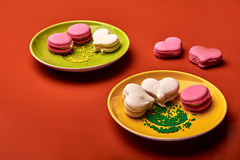 Traditional french colorful macarons on the yellow and green plates Royalty Free Stock Image