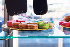 Traditional french colorful macaroons in confectionery shop. Display of delicious pastries in a bakery. Stock Photos