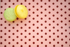 Traditional french colorful macaroons in a row on polka dots pink background Royalty Free Stock Photos