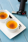 Traditional French creme brulee and blowtorch Stock Images