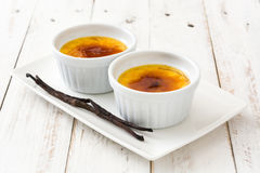 Traditional French creme brulee dessert with caramelized sugar on top. On white wooden table stock image