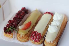 Traditional French dessert. Beautiful eclairs with icing and berries. stock photo
