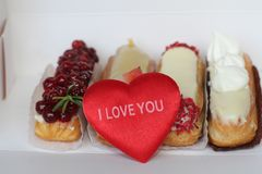 Traditional French dessert with plush heart and an inscription I Love You. Beautiful eclairs with icing and berries. Traditional French dessert with plush heart Stock Photo