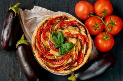 Traditional French dish quiche with vegetables and cheese on the black background. Vegetarian tart decorated with fresh eggplants. Tomatoes and basil leaves royalty free stock images