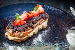 Traditional french eclairs served on premium dark plate. Food for breakfast with copy space. Close up profitroles classic. eclair. With strawberry and truffle royalty free stock image