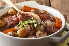 Traditional French food: Coq au vin with wine and vegetable Stock Photos