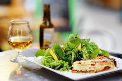 Traditional French food: quiche lorraine and fresh salad leaves with glass of beer on background. Traditional French food: quiche lorraine and fresh salad leaves Royalty Free Stock Photos