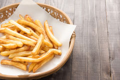 Traditional french fries in basket on wooden background Royalty Free Stock Images