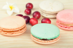 Traditional French Macarons with cranberries. Traditional French Macaroons with cranberries on wooden background Stock Photos