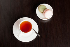 Traditional french macrons with tea set on the background. Close up, horizontal Stock Images